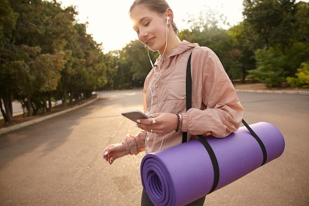 Foto di giovane donna che cammina dopo lo yoga al parco, tiene in mano lo smartphone e chiacchiera con un amico spiritoso, ascolta musica in cuffia, sorridendo ampiamente.