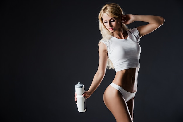 Photo of young woman wearing sportswear with bottle, standing against of dark backround.  shot