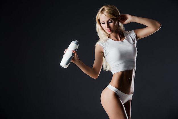 Photo of young woman wearing sportswear with bottle, standing against of dark