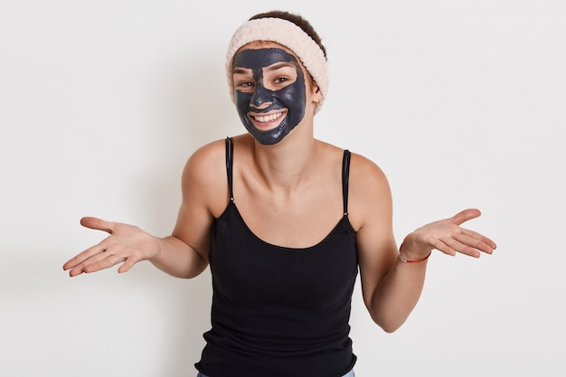 Photo of young woman with charming smile spreading palms aside, shows helpless gesture, wears nourishing facial mask for reducing wrinkles, poses against white wall.