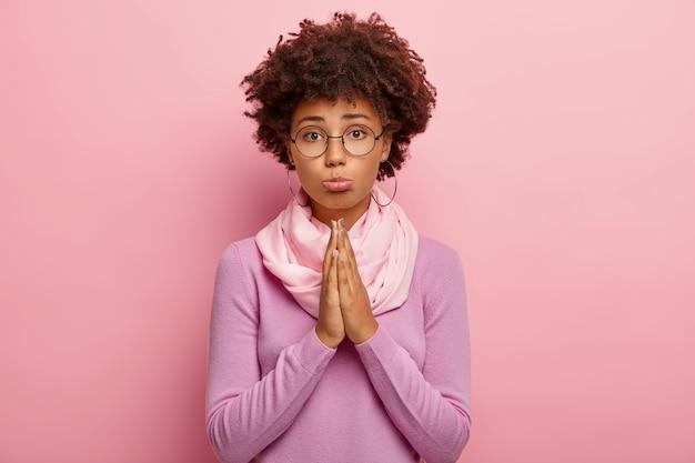 Foto di una giovane donna con la pelle scura e l'acconciatura afro, ha un'espressione pietosa, tiene i palmi premuti insieme, chiede di dare un'altra possibilità, crede in meglio, indossa occhiali rotondi, maglione viola
