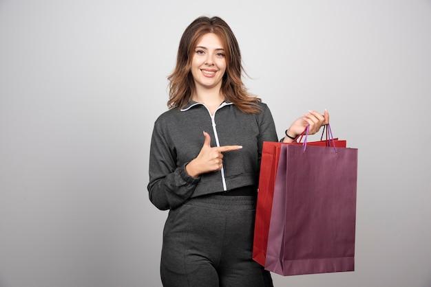 Foto di giovane donna con borse della spesa e agitando la mano.