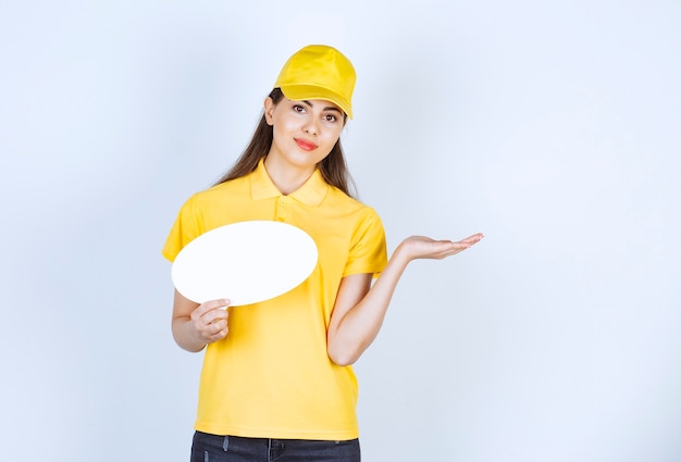Photo of young woman in yellow uniform holding empty speech bubble over white wall.