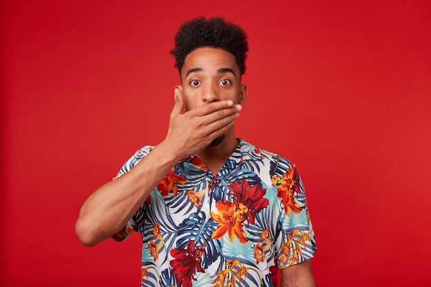 Photo of young wondered african american man, wears in hawaiian shirt, looks at the camera with surprised expression, covered mouth with palms, stands over red background.