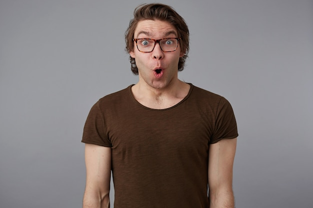 Photo of young wondered handsome man with glasses wears in basic t-shirt, stands over gray background and broadly smiles, looks happy and surprised.