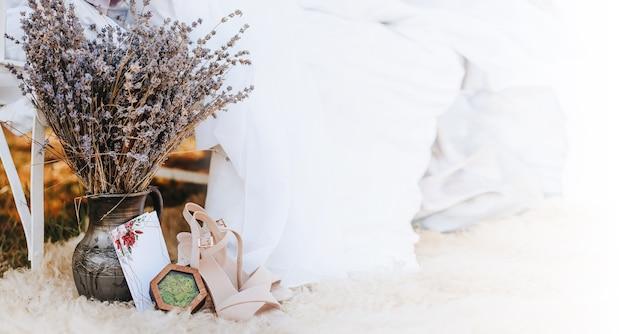 靴、花、自然への招待状が付いたフォトゾーンの天蓋付きベッド。生地が風になびく。花嫁の写真のための場所。撮影会