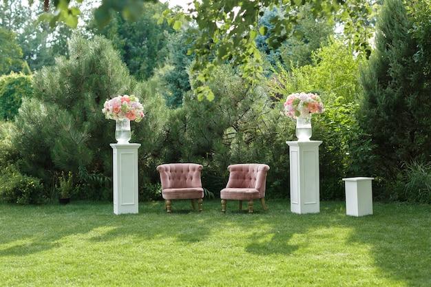 꽃과 나무 큐브로 장식 된 결혼식에서 아름다운 안락 의자가있는 포토 존