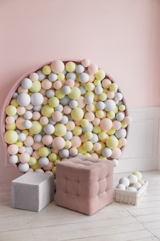 Photo zone with pouf and colorful balls on wall. pink, gray and yellow balls on wall, soft colors.