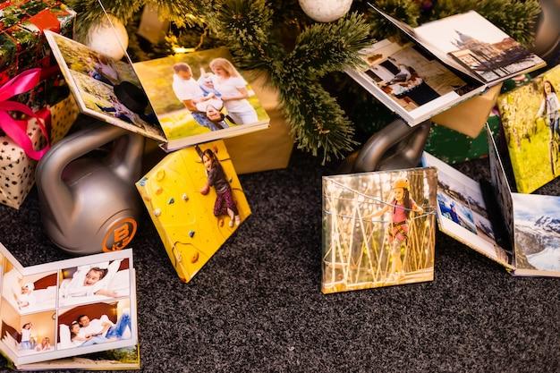 ギフトホリデーとしてクリスマスツリーの近くのスポーツのための写真集、アルバム、ウェイト
