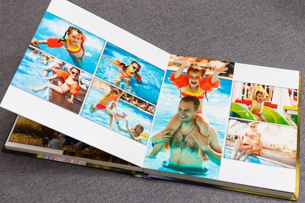 Photobook album on deck table with travel photos