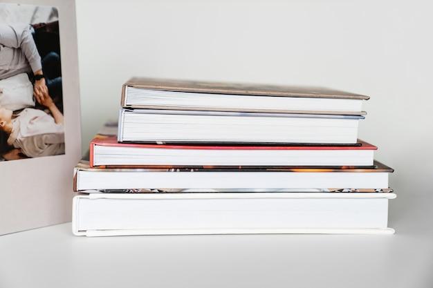 Фотокниги, сложенные друг на друга на белом столе. фотографическая и полиграфическая продукция. печать книг и фотоальбомов после фотосессии.