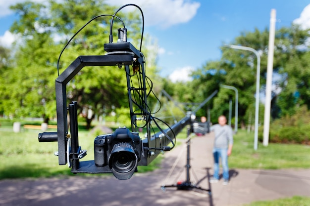 Photocamera on the platform close-up and blurred videographer, use camera crane in the park at summer day