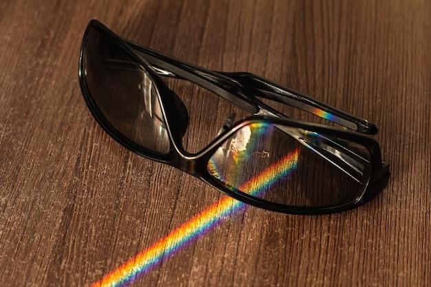 나무 테이블 위의 광 변색 유리는 무지개 스펙트럼으로 분해 된 햇빛 광선을 교차합니다. 선택적 초점