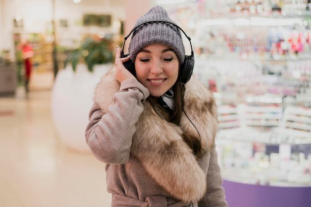 Photogenic женщина улыбается с heaphones в торговом центре0