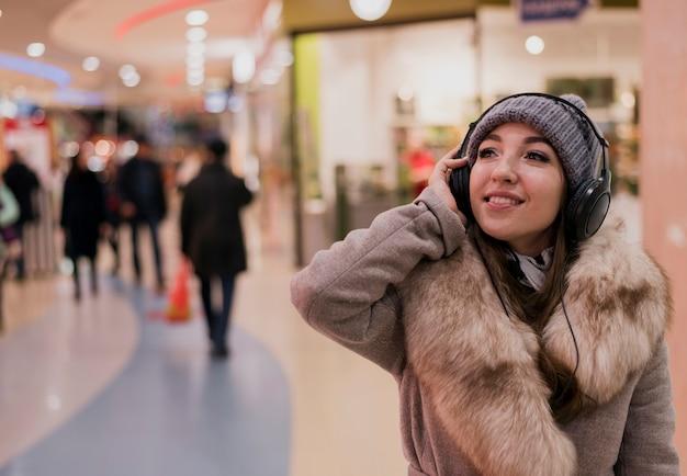 Фотогеничная женщина с наушниками в торговом центре