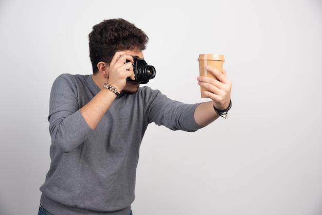 Fotografa tenendo in mano una tazza di caffè in plastica per scattare foto.