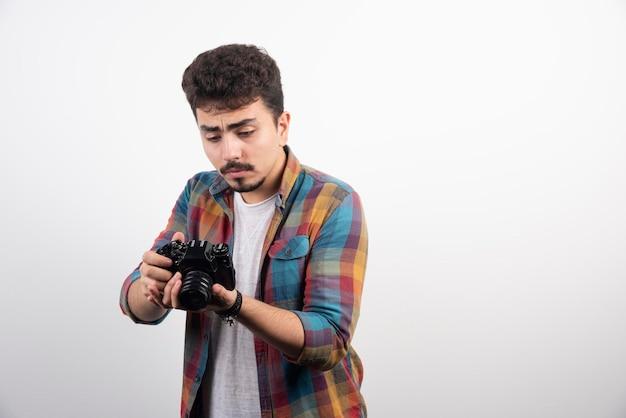 彼のカメラを見て考えている写真。