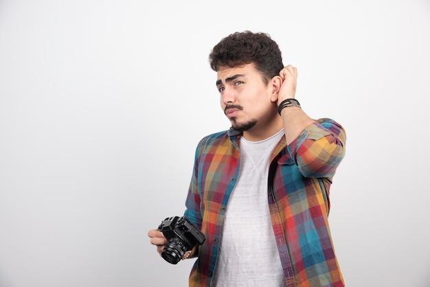 Фотограф смотрит в камеру и думает.