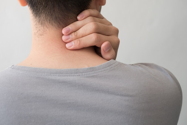 Photograph of a man from the back with pain and neck injury