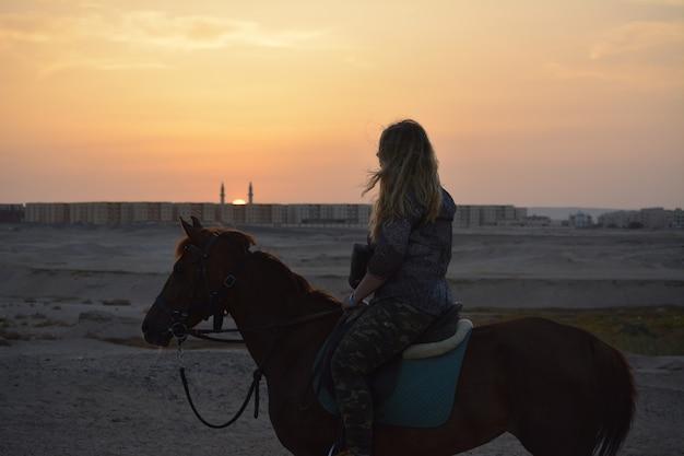 석양을 바라 보는 말을 타는 소녀의 사진