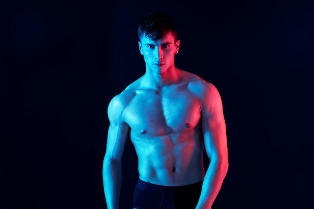 운동 체격과 네온 피부색 격리된 배경 잘린 보기를 가진 남자의 사진