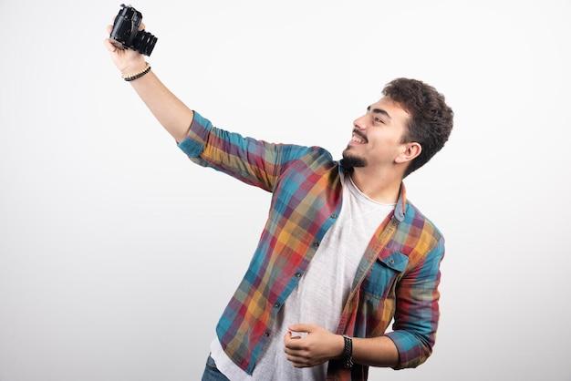 Fotografa scattando i suoi selfie in modo positivo con una macchina fotografica.
