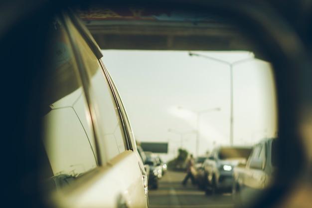車の後ろの交通のバックミラーを通して写真を撮ります。