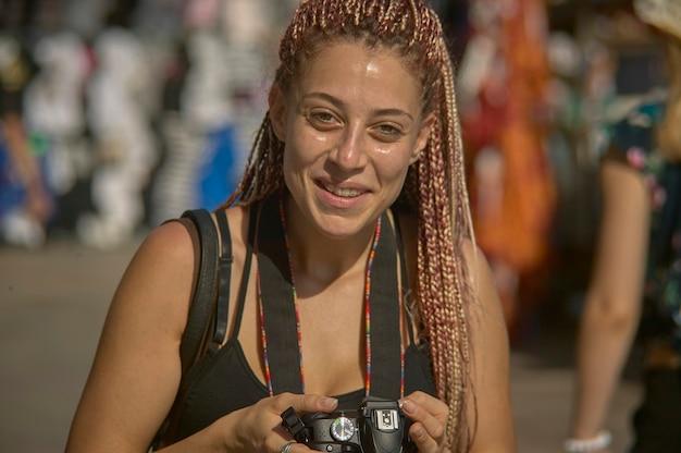 Фотография с косичками снимает уличное фото днем