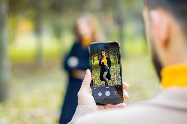 秋の公園で電話でガールフレンドの写真を撮る