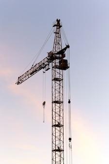 На фото крупным планом строительные краны во время строительства нового многоэтажного жилого дома