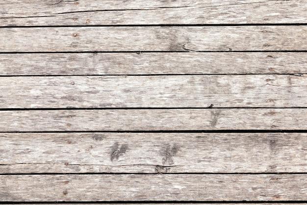 板で作られた写真のクローズアップの古い床。戸外にあるので木は灰色でした