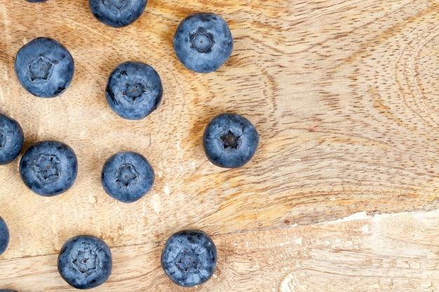 촬영 된 근접 촬영 수확 익은 블루 베리, 열매는 상단의 사진에서 오래 된 나무 보드에 펼쳐져 있습니다.
