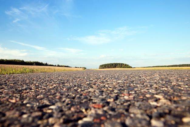 새로운 아스팔트 도로를 촬영했습니다. 아래에서 찍은 사진은 작은 돌과 타르 얼룩을 볼 수 있습니다.