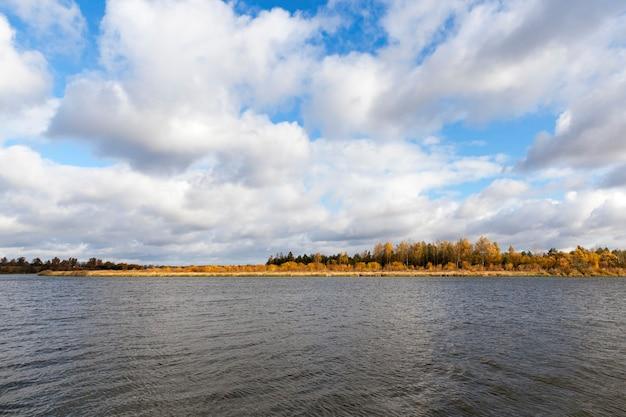 Сфотографировал реку неман, расположенную в беларуси, осенний сезон, лес и деревья пожелтели в пасмурную погоду.