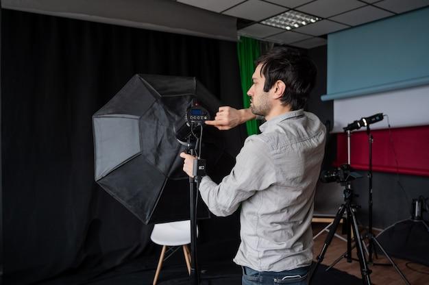 写真家はスタジオでソフトボックスの光の強さを調整します。写真撮影の準備をしている写真機材を設定する男。