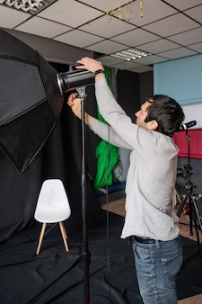 Photographer adjust softbox light intensity in studio. man setting photographing equipment getting ready for a photo shoot.