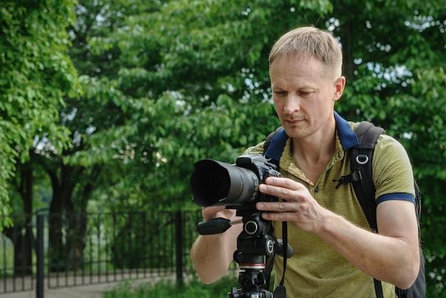 Photographer adjusting camera on tripod