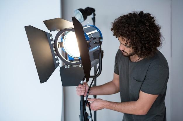 Фотограф регулирует прожектор