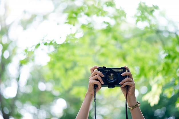 Фотограф и любитель фотоаппаратов черный фотоаппарат и естественный зеленый фон