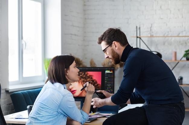 노트북, 모니터, 그래픽 드로잉 태블릿 및 색상 팔레트를 사용하여 사무실에서 일하는 사진 작가 및 그래픽 디자이너. 광고 대행사에서 아이디어를 논의하는 팀 만들기. 이미지 수정. 팀워크.
