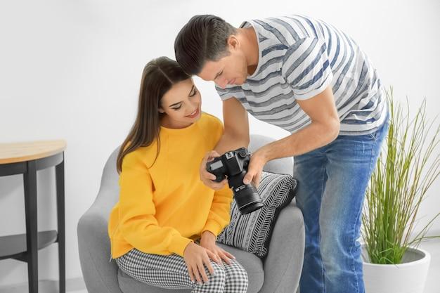 전문 스튜디오에서 카메라 디스플레이에 사진을 논의하는 사진 작가와 모델