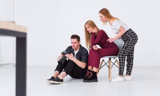 Фотограф и модели смотрят на фотографии в студии