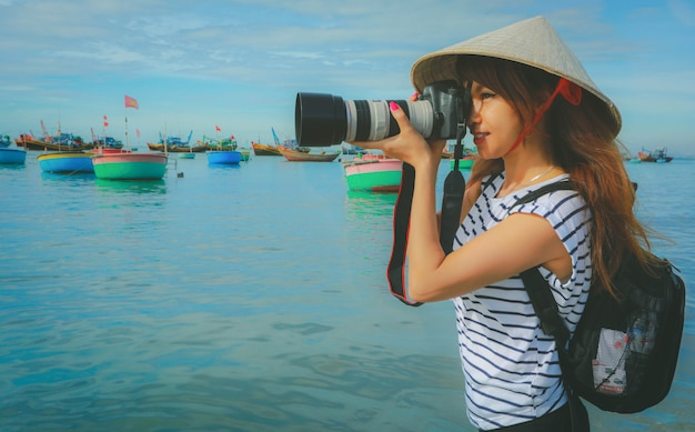Photographer asian woman taking photos with camera professional photography in mui ne, fishing village with traditional vietnamese boats, vietnam