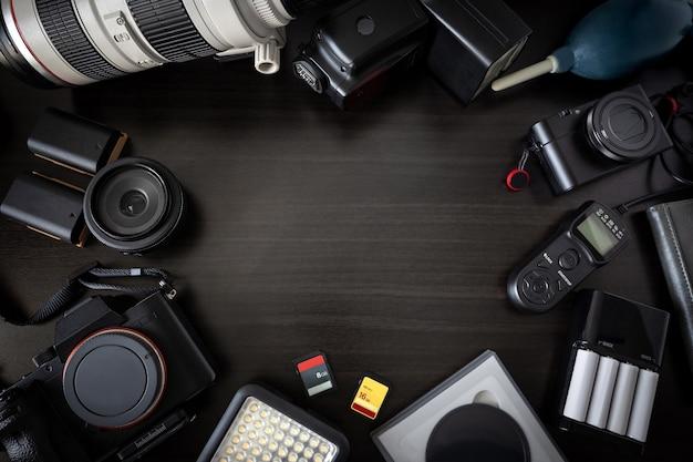 카메라 렌즈와 많은 액세서리와 나무 배경에 설정된 사진 배낭