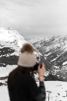 Photographer capturing the view of snowy mountains