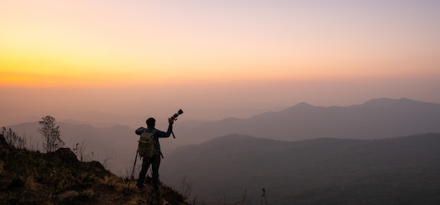 Photographer celebrating success on top of a mountain in a majestic sunrise