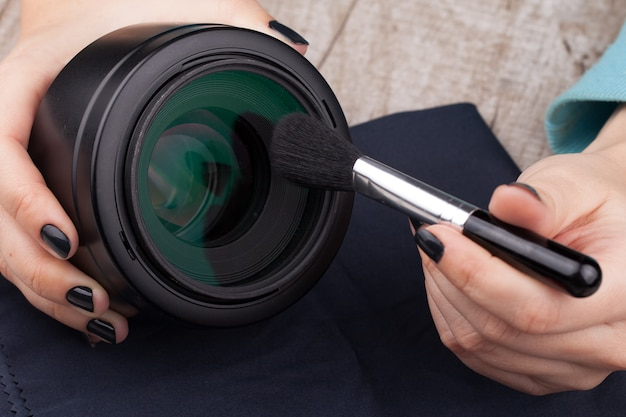 The photographer cleans the lens of the lens from dust.
