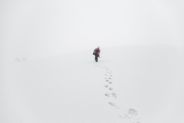 Photographer climbs the snow-covered slope of the mountain with the equipment in the fog.