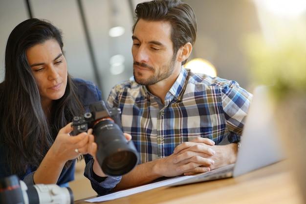 Photographer colleagues going through photos on camera