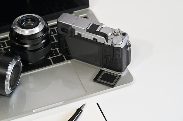 Photographer desk with camera, lens, laptop and memory.